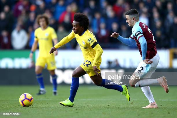 Willian of Chelsea runs with the ball past Matthew Lowton of Burnley during the Premier League match between Burnley FC and Chelsea FC at Turf Moor...