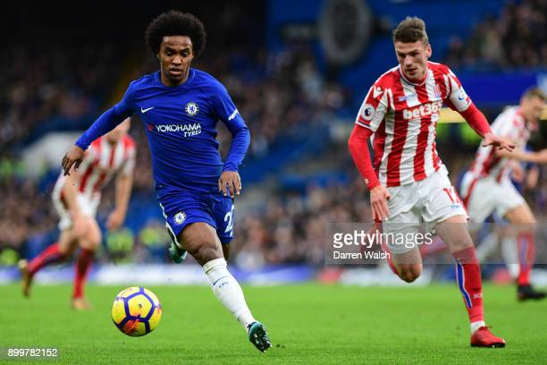 Willian of Chelsea runs with the ball under pressure from Josh Tymon of Stoke City during the Premier League match between Chelsea and Stoke City at...