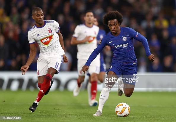 Willian of Chelsea runs with the ball under pressure from ...