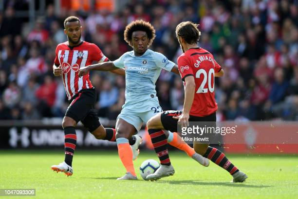 Willian of Chelsea runs with the ball under pressure from Manolo Gabbiadini and Ryan Bertrand of Southampton during the Premier League match between...