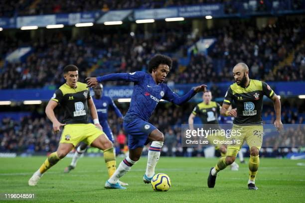 Willian of Chelsea runs with the ball under pressure from Nathan Redmond of Southampton during the Premier League match between Chelsea FC and...