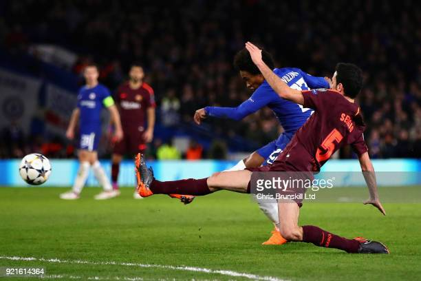 Willian of Chelsea takes a shot that hits the post as Sergio Busquets of FC Barcelona dives in to attempt to block during the UEFA Champions League...