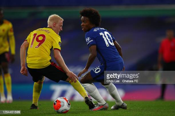 Willian of Chelsea turns away from Will Hughes of Watford during the Premier League match between Chelsea FC and Watford FC at Stamford Bridge on...