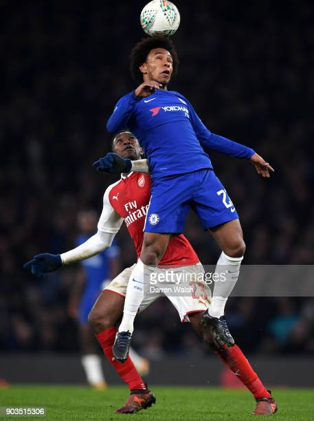 Willian of Chelsea wins a header ahead of Danny Welbeck of Arsenal during the Carabao Cup SemiFinal First Leg match between Chelsea and Arsenal at...
