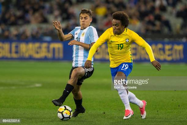 Willian Silva of the Brazilian National Football Team and Paulo Ezequiel Dybala of the Argentinan National Football Team contest the ball during the...