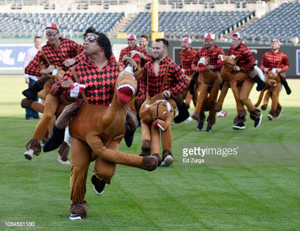 Willians Astudillo of the Minnesota Twins leads other rookies as they have a derby race on the infield at Kauffman Stadium after their game against...
