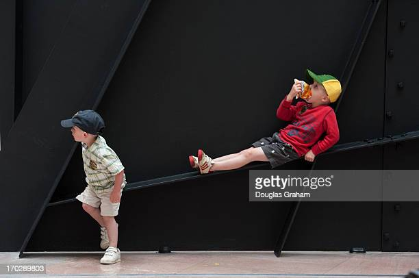 Willie and Henry Gunlock play on the Alexander Calder's sculpture Mountains and Clouds in the atrium of the Hart Senate Office building on June 10...