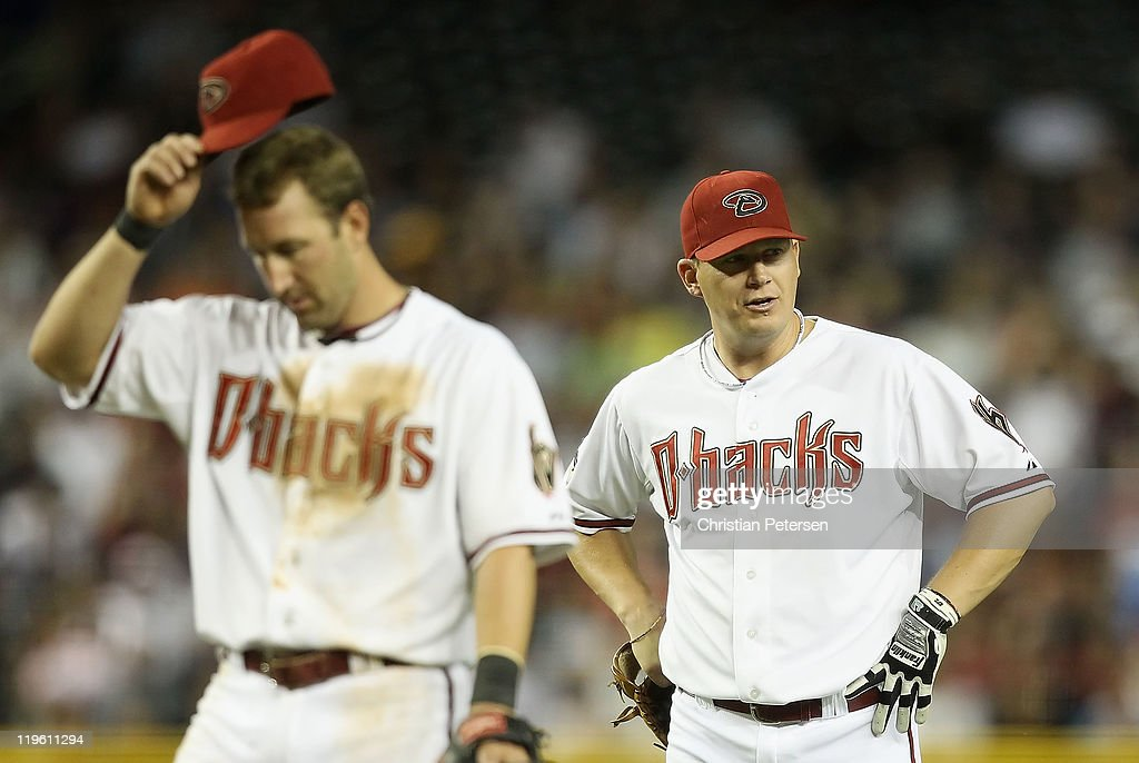 Willie Bloomquist #18 and Geoff Blum #27 of the Arizona Diamondbacks react during a pitching change in the Major League Baseball game against the Colorado Rockies at Chase Field on July 22, 2011 in Phoenix, Arizona.