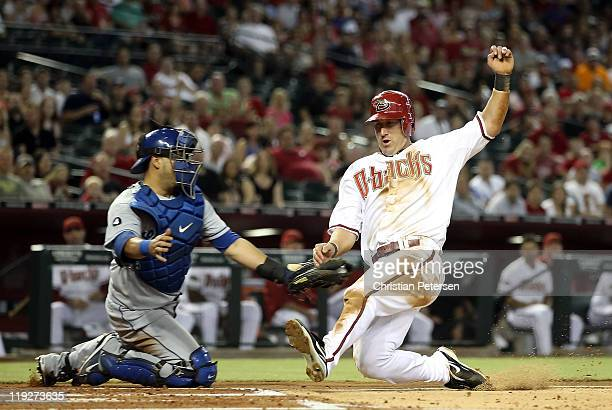 Willie Bloomquist of the Arizona Diamondbacks is tagged out at home plate by catcher Dioner Navarro of the Los Angeles Dodgers during the first...