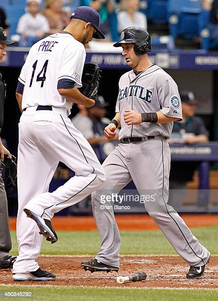 Willie Bloomquist of the Seattle Mariners crosses the plate in front of pitcher David Price of the Tampa Bay Rays to score off of a tworun single by...