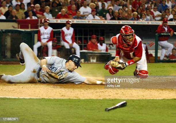 Willie Bloomquist of the Seattle Mariniers slides beneath tag of Los Angeles Angels of Anaheim catcher Bengie Molina to score in the fifth inning of...