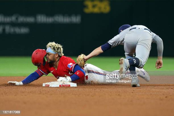 Willie Calhoun of the Texas Rangers slides into second as Brandon Lowe of the Tampa Bay Rays applies the tag in the fourth inning at Globe Life Field...