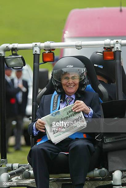 Willie Carson in unusal head gear reads the paper before the start of todays racing at Epsom Racecourse on June 6 2003 in Epsom England