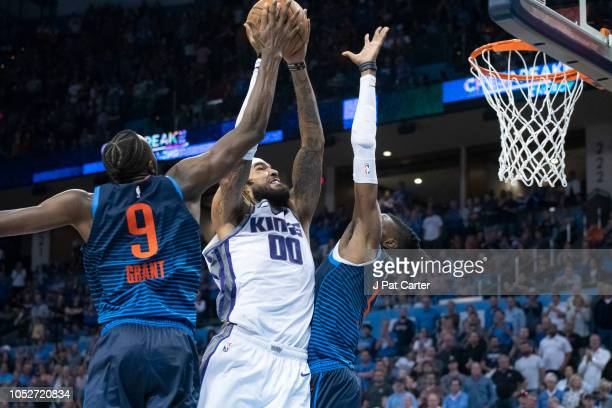 Willie CauleyStein of the Sacramento Kings goes between Jerami Grant of the Oklahoma City Thunder and Nerlens Noel of the Oklahoma City Thunder...