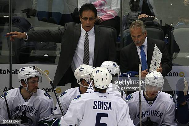 Willie Desjardins of the Vancouver Canucks directs the team along with assistant coach Doug Lidster during a time out against the Colorado Avalanche...