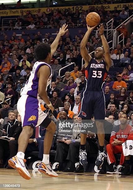 Willie Green of the Atlanta Hawks puts up a three point shot over Josh Childress of the Phoenix Suns during the NBA game at US Airways Center on...