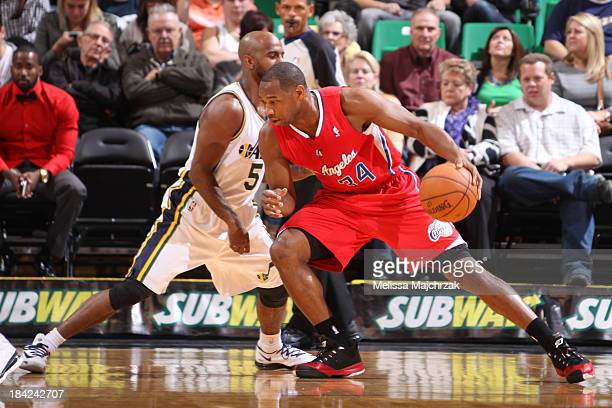 Willie Green of the Los Angeles Clippers drives against John Lucas III of the Utah Jazz at EnergySolutions Arena on October 12, 2013 in Salt Lake...