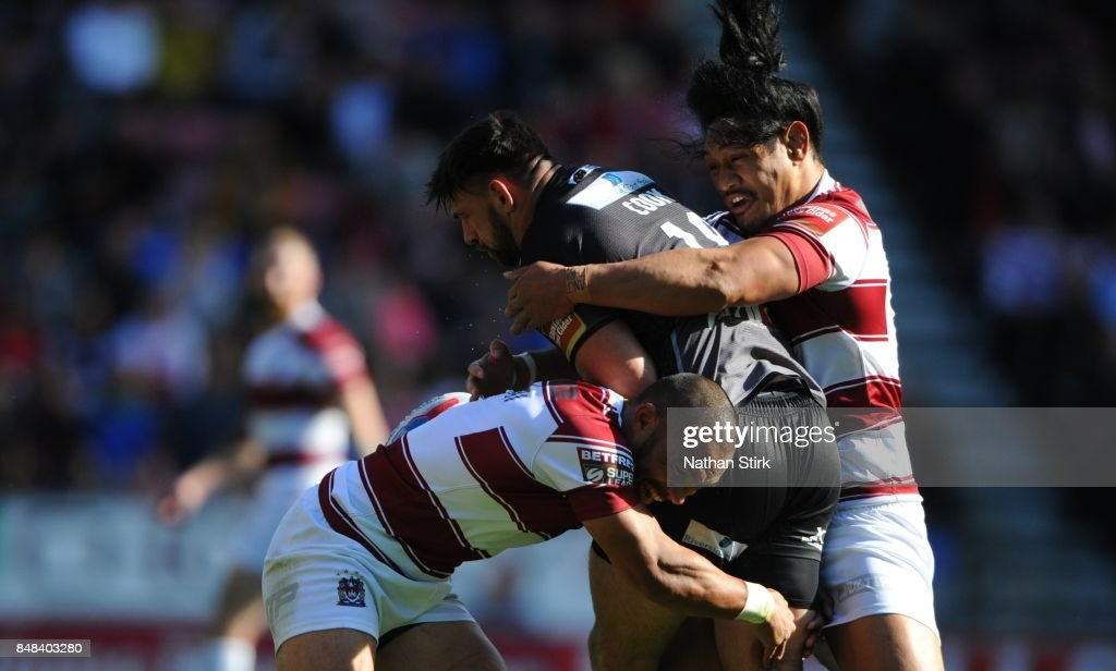 Willie Isa (L) and Taulima Tautai (R) of Wigan tackle Matt Cook of Castleford Tigers during the Betfred Super League Super 8s Round 6 match between Wigan Warriors and Castleford Tigers at DW Stadium on September 17, 2017 in Wigan, England.