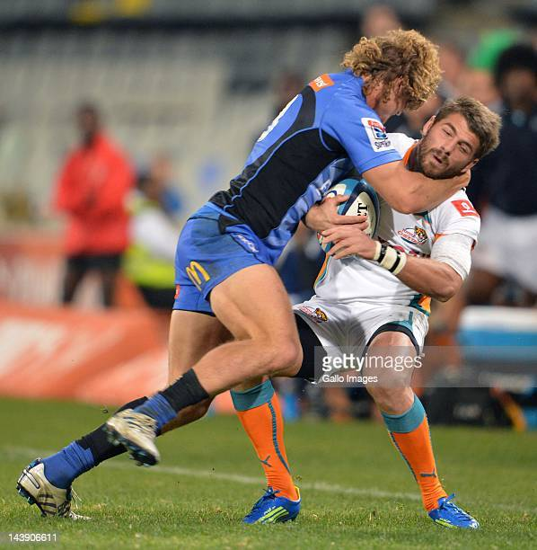 Willie le Roux of the Cheetahs is tackled by Nick Cummins of the Force during the Super Rugby match between Toyota Cheetahs and Force at Free State...
