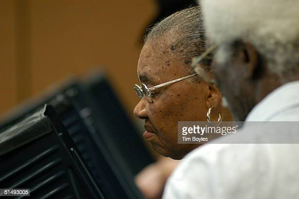 Willie Mae Fletcher uses an electronic machine to cast her ballot as her husband AC Fletcher looks over her shoulder on the first day of early voting...