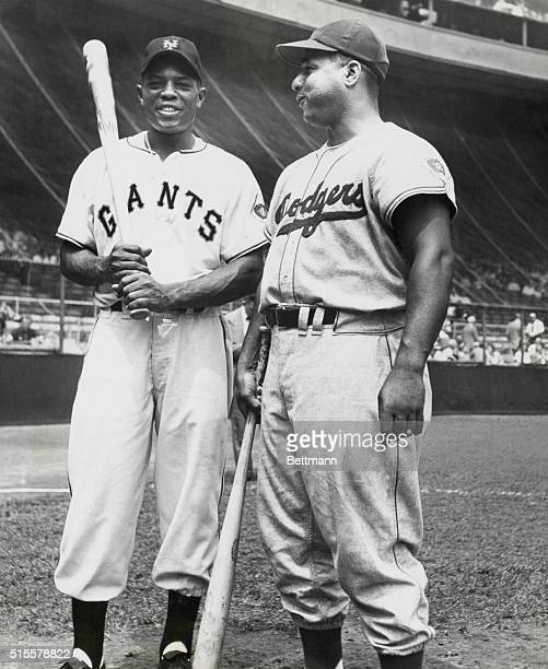 Willie Mays of the New York Giants and Roy Campanella of the Brooklyn Dodgers photographed together on the playing field in the early 50's,...
