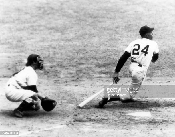 Willie Mays of the New York Giants swings at the pitch as catcher Yogi Berra of the New York Yankees sets up behind home plate during Game 1 of the...