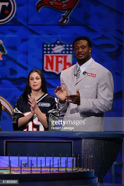 Willie McGinest of the New England Patriots applauds with his favorite Patriots fan during the Wheel of Fortune NFL Players Week taping on December 7...