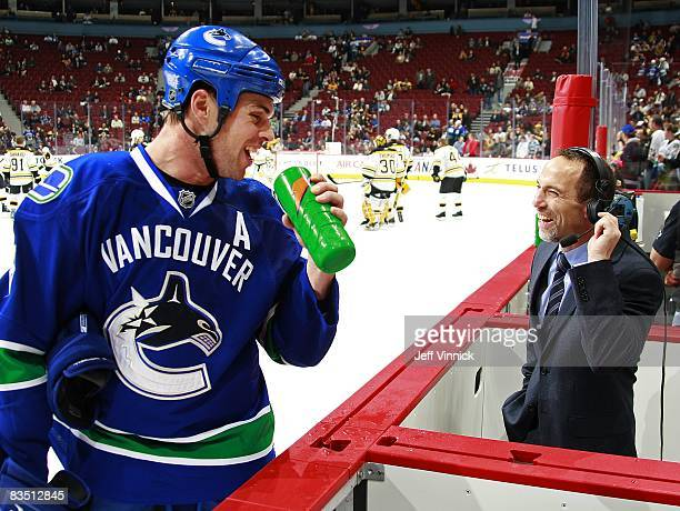 Willie Mitchell *8 of the Vancouver Canucks laughs with TSN announcer Ray Ferraro during the game against the Boston Bruins at General Motors Place...
