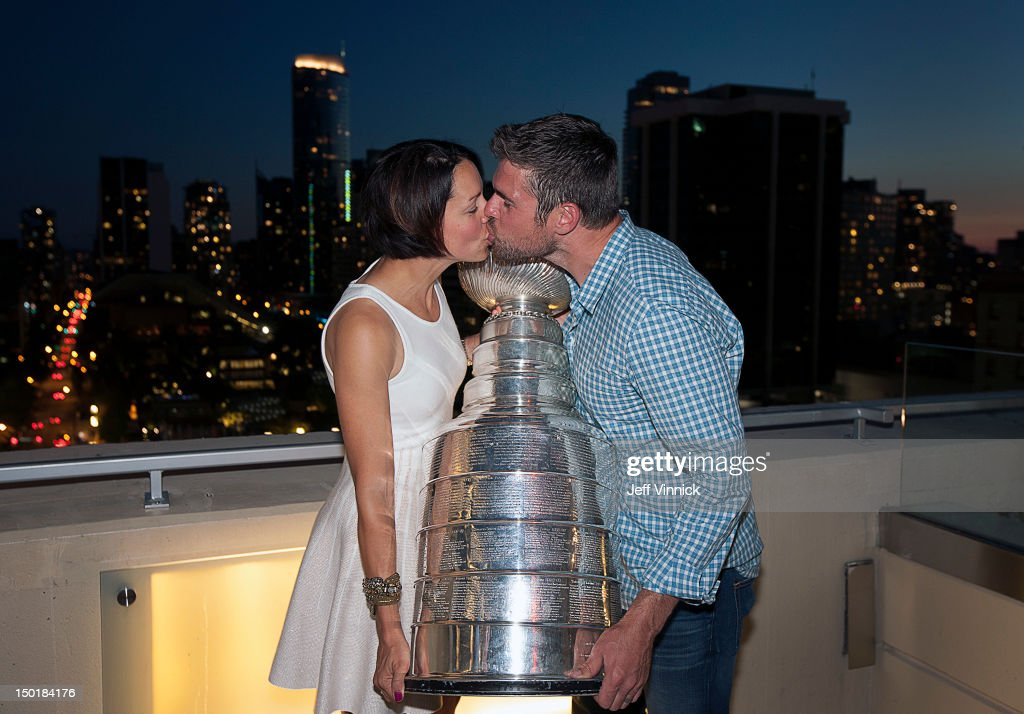Willie Mitchell #33 of the Los Angeles Kings and his wife Megan Mitchell kiss as they hold the Stanley Cup during a visit to the Rosewood Hotel Georgia August 11, 2012 in Vancouver, British Columbia, Canada.