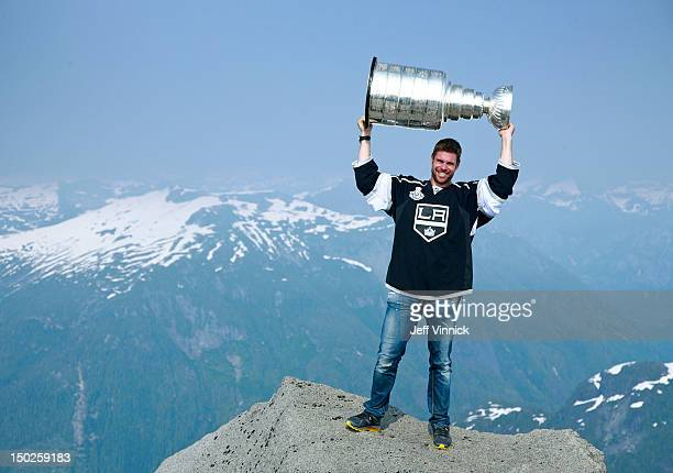 Willie Mitchell of the Los Angeles Kings holds up the Stanley Cup at the top of Mount Benedict August 12, 2012 near Port McNeill, British Columbia,...