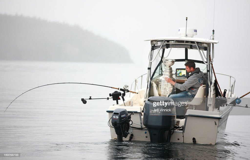 Willie Mitchell #33 of the Los Angeles Kings reads the names on the Stanley Cup as he goes fishing August 12, 2012 in Telegraph Cove, British Columbia, Canada. Mitchell took the Stanley Cup to his hometown of Port McNeill, B.C. for his one-day celebration with the prized trophy.