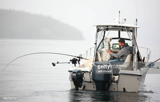 Willie Mitchell of the Los Angeles Kings reads the names on the Stanley Cup as he goes fishing August 12, 2012 in Telegraph Cove, British Columbia,...