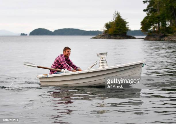 Willie Mitchell of the Los Angeles Kings sits with the Stanley Cup as he paddles a rowboat August 12, 2012 in Telegraph Cove, British Columbia,...