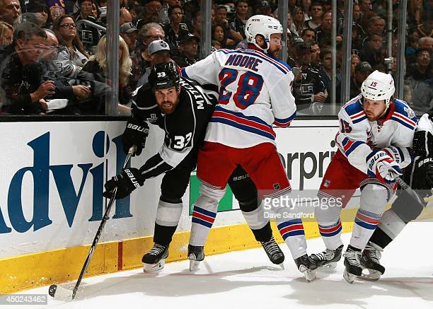 Willie Mitchell of the Los Angeles Kings tries to get around Dominic Moore of the New York Rangers in the first period of Game Two of the 2014...