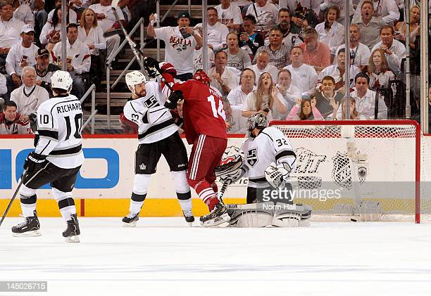 Willie Mitchell of the Los Angeles Kings tries to move Taylor Pyatt of the Phoenix Coyotes from the crease as teammate Jonathan Quick watches the...