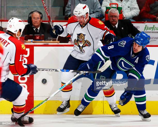Willie Mitchell of the Vancouver Canucks and Keith Ballard of the Florida Panthers battle for the puck during their game at General Motors Place on...