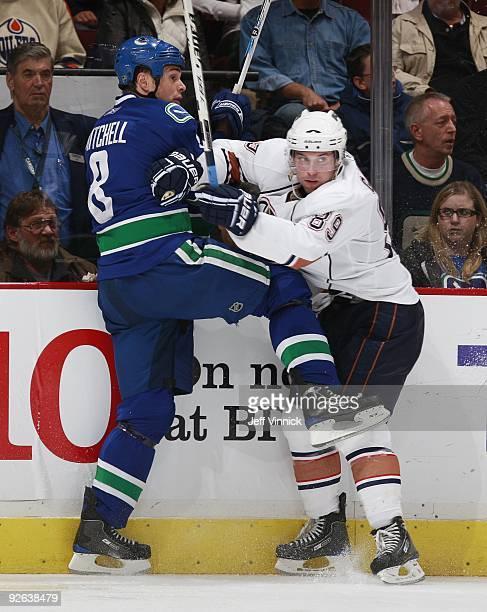 Willie Mitchell of the Vancouver Canucks checks Sam Gagner of the Edmonton Oilers during their game at General Motors Place on October 25, 2009 in...