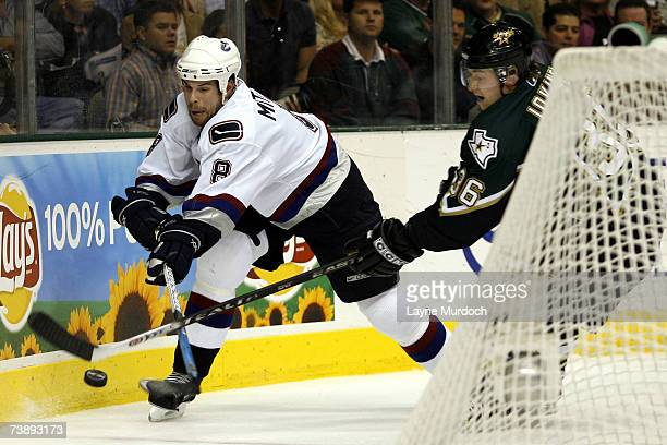 Willie Mitchell of the Vancouver Canucks fights for the puck with Jussi Jokinen of the Dallas Stars during the 1st period of game three of the 2007...