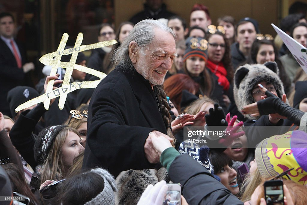 Willie Nelson greets fans when Kesha performs on NBC's 'Today' at Rockefeller Plaza on November 20, 2012 in New York City. Host Savannah Gutherie looks on.