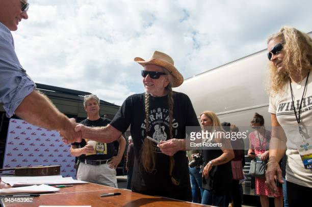 Willie Nelson signs a poster backstage at Farm Aid at the KeyBank Pavilion in Burgettstown Pennsylvania United States on September 16 2017 On the...