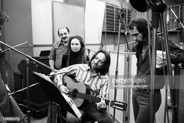 Willie Nelson with guitar is accompanied in a recording session by producer Arif Mardin pianist and singer Bobbie Nelson and drummer Paul English in...