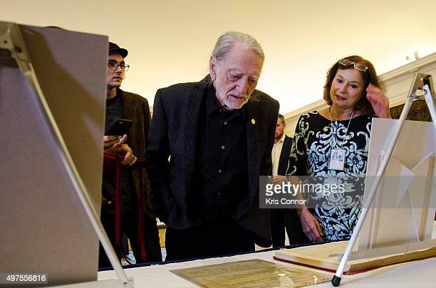 Willie Nelson with wife Annie D'Angelo check out artifacts after attending the 2015 Gershwin Prize Luncheon where he was honored with a certificate...