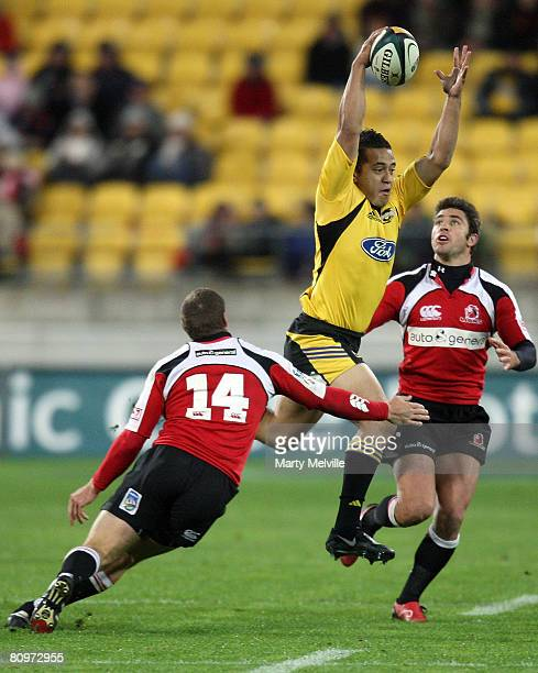 Willie Ripia of the Hurricanes jumps for a high pass as he gets tackled by Jannie Boshof of the Lions during the round 12 Super 14 match between the...