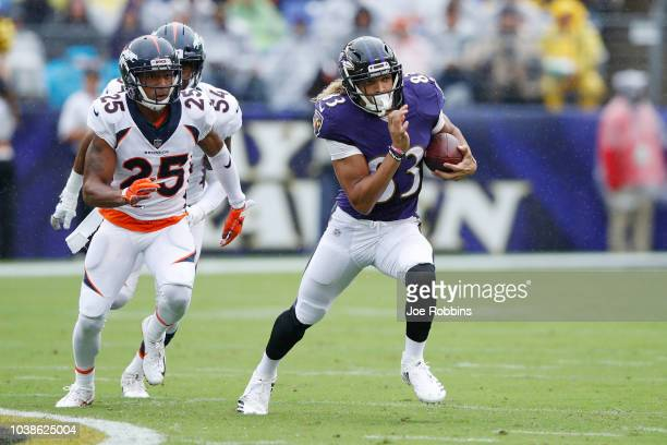 Willie Snead IV of the Baltimore Ravens runs with the ball after catching a pass ahead of Chris Harris Jr #25 of the Denver Broncos in the first...