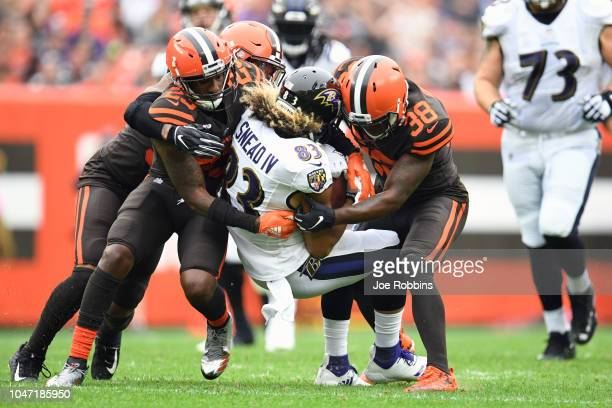 Willie Snead of the Baltimore Ravens is tackled by Damarious Randall of the Cleveland Browns and TJ Carrie of the Cleveland Browns in the first half...