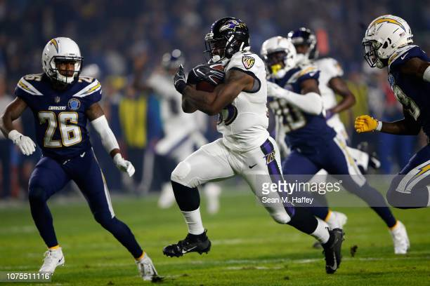 Willie Snead of the Baltimore Ravens runs the ball as Casey Hayward of the Los Angeles Chargers looks to defend during the first half of a game at...