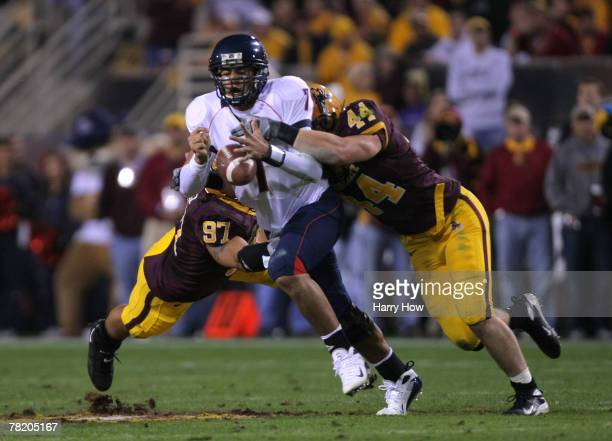 Willie Tuitama of the University of Arizona Wildcats fumbles the ball as he is tackled by Travis Goethel and Luis Vasquez of the Arizona State...