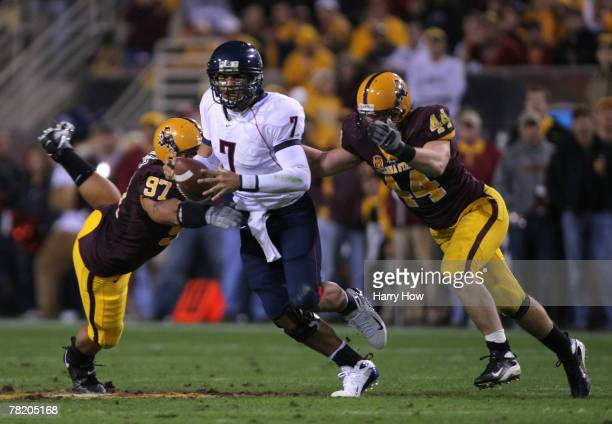 Willie Tuitama of the University of Arizona Wildcats is pressured by Travis Goethel and Luis Vasquez of the Arizona State University Sun Devils...