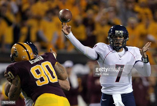 Willie Tuitama of the University of Arizona Wildcats pass over David Smith of the Arizona State University Sun Devils during the first quarter at Sun...