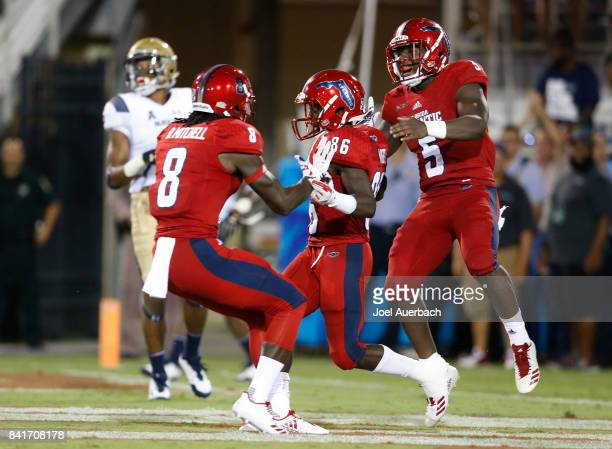 Willie Wright is congratulated by Bobby Mitchell and Devin Singletary of the Florida Atlantic Owls after scoring a touchdown against the Navy...